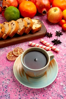 ピンクの机の上にスライスしたケーキとお茶を正面から見たおいしいフルーツの組成物