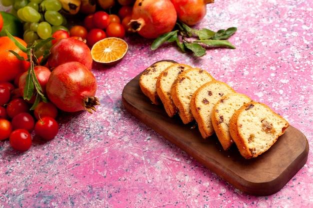Вид спереди вкусная фруктовая композиция с нарезанными тортами на светло-розовом столе