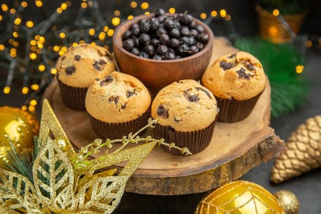 Vista frontale deliziose torte fruttate intorno ai giocattoli dell'albero delle vacanze su sfondo scuro torta da dessert crema fotografica dolce