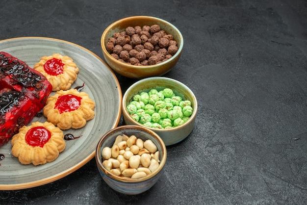 Vista frontale deliziose torte fruttate dolci con biscotti e caramelle sullo spazio buio