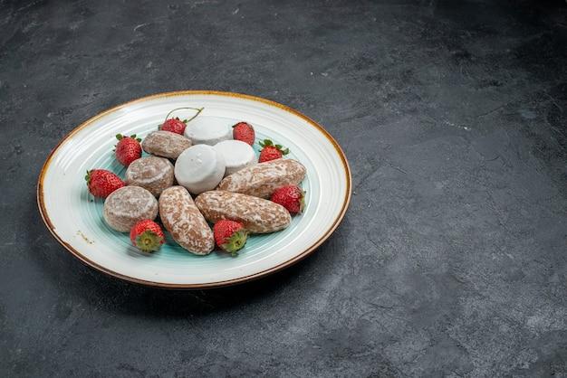 Вид спереди вкусные имбирные пряники со свежей красной клубникой на темно-сером письменном торте, печенье, сахар, сладкий пирог, выпечка, печенье