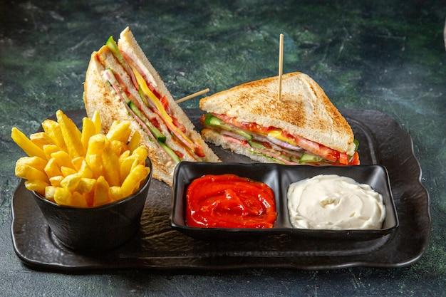 Vista frontale deliziosi panini al prosciutto con patatine fritte e condimenti superficie scura