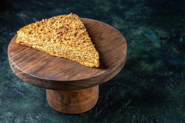 Front view delicious honey cake slice of it on round wooden board dark surface