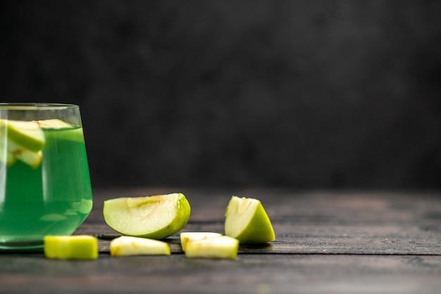 Vista frontale di un delizioso succo in un bicchiere e una mela tritata su sfondo scuro