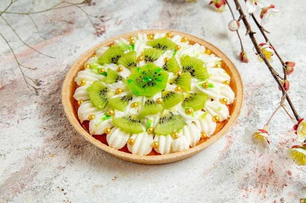 ホワイト クリームとスライスしたキウイを明るいホワイト スペースに入れた正面のおいしいキウイ デザート