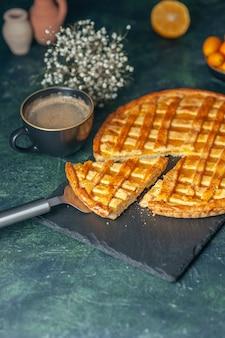 Vista frontale deliziosa torta kumquat con un pezzo affettato sulla superficie blu scuro dessert al forno dolce cuocere la pasta biscotto colore torte del tè biscotto