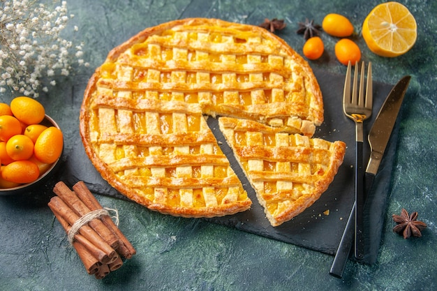 Front view delicious kumquat pie with sliced one piece on a dark surface dessert sweet bake cookie tea cake dough oven biscuit color