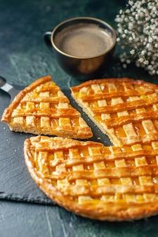 Вид спереди вкусный пирог с кумкватом с нарезанным одним кусочком на темно-синей поверхности печь десерт сладкое тесто бисквит цветной чайный торт печенье