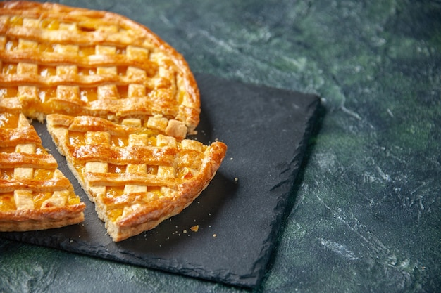 Вид спереди вкусный пирог с кумкватом с нарезанным одним кусочком на темной поверхности десерт сладкая выпечка печенье чай торт бисквитный цвет тесто печь