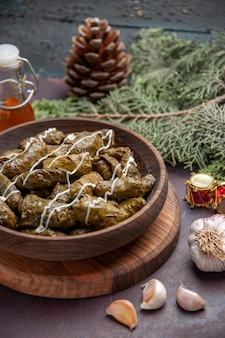 Front view delicious leaf dolma meat dish with seasonings on a dark space