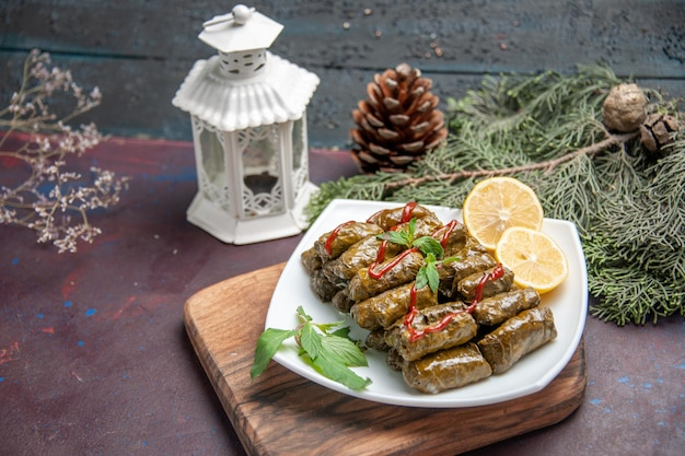 Front view delicious leaf dolma with lemon slices on a dark space