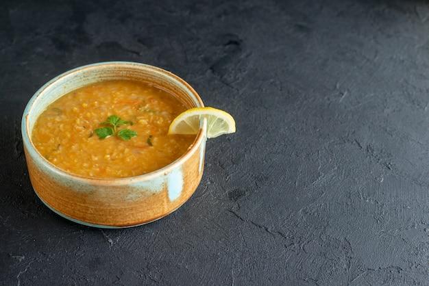 暗い表面の小さなプレートの中にレモンスライスが入った正面図のおいしいレンズ豆のスープ