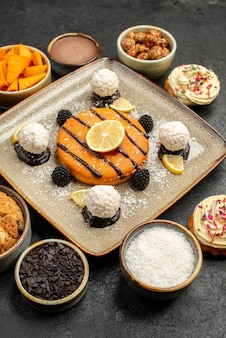 Vista frontale deliziosa piccola torta con caramelle al cocco su sfondo scuro torta da tè biscotto biscotto torta dessert