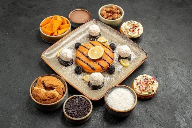正面図濃い灰色の背景のケーキデザートビスケットパイクッキーティーにココナッツキャンディーとおいしい小さなケーキ