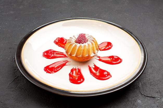 正面図暗い背景茶甘いビスケットシュガーパイクッキーのプレートの内側に赤いアイシングとおいしい小さなケーキ