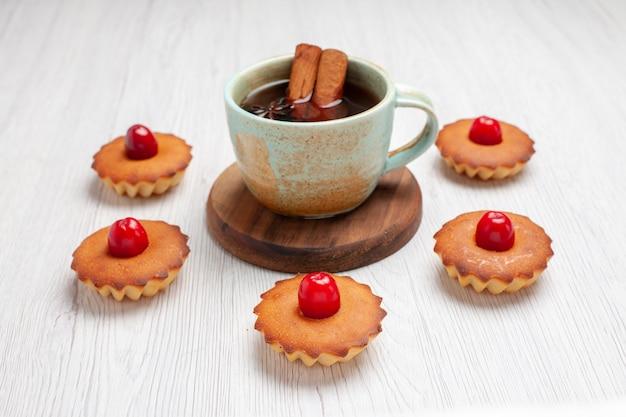 Vista frontale deliziose torte con la tazza di tè sul biscotto dolce dessert torta bianca scrivania