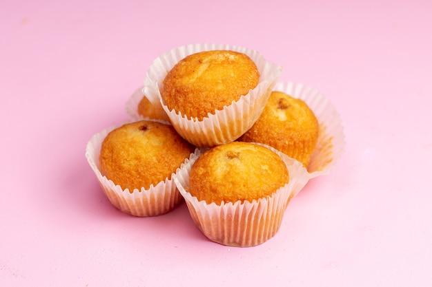 Вид спереди вкусные маленькие пирожные с фруктовой начинкой на розовом фоне торт бисквитное печенье сладкий сахарный чай