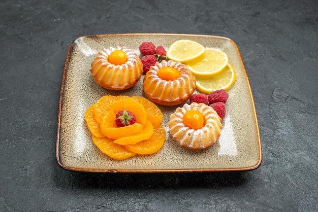 어두운 공간에 레몬 슬라이스와 귤과 함께 전면보기 맛있는 작은 케이크