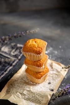 Una vista frontale deliziose torte con fiori viola sullo zucchero dolce del biscotto del tè del biscotto della tavola grigia
