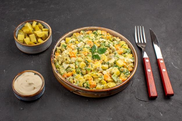 Vista frontale della deliziosa insalata di maionese sulla superficie scura