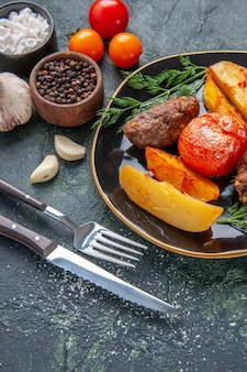 Front view of delicious meat cutlets baked with potatoes and tomatoes on a black plate cutlery set spices garlics tomatoes on green black mixed colors background