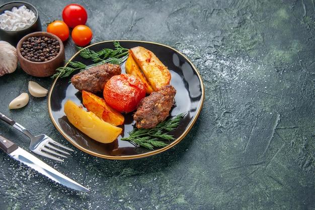 Vista frontale di deliziose cotolette di carne al forno con patate e pomodori su un piatto nero set di posate spezie garlics pomodori sul lato destro