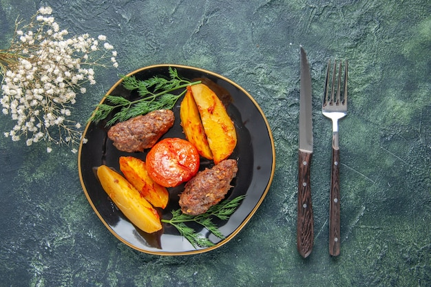 Front view of delicious meat cutlets baked with potatoes and tomatoes on a black plate cutlery set white flowers on green black mixed colors background