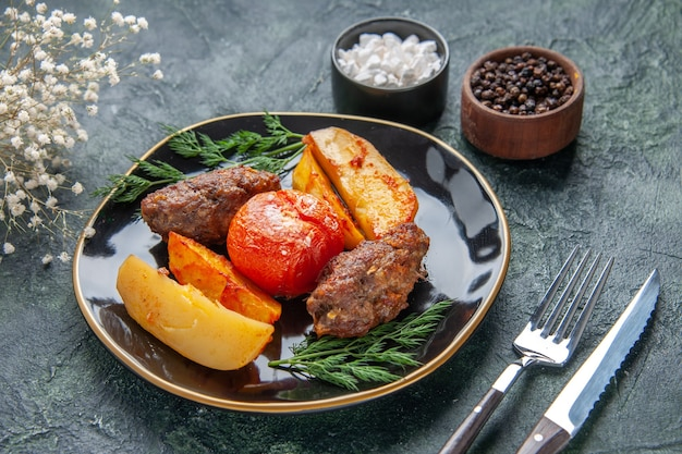 Front view of delicious meat cutlets baked with potatoes and tomatoes on a black plate cutlery set white flowers spices on green black mixed colors background