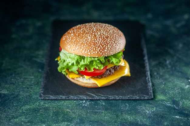 Front view delicious meat hamburger with green salad cheese and tomatoes on dark background