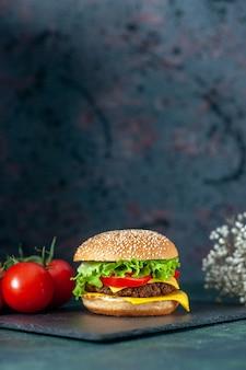 Vista frontale delizioso hamburger di carne con pomodori rossi su sfondo scuro