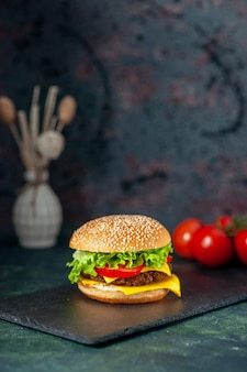 Front view delicious meat hamburger with red tomatoes on dark background