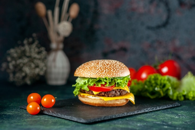 Вид спереди вкусный мясной гамбургер с красными помидорами на темном фоне