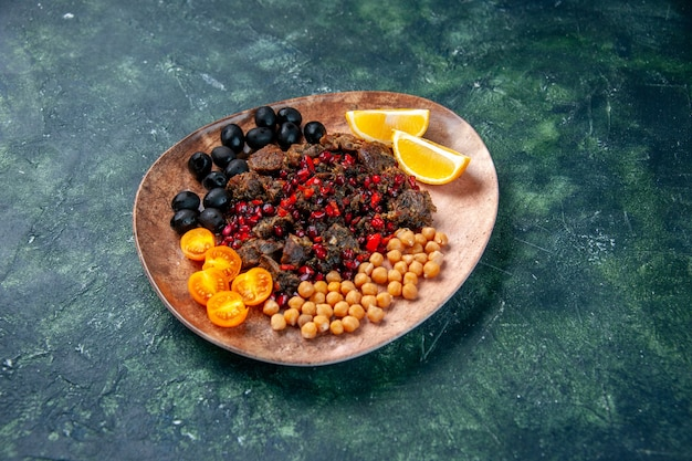 Front view delicious meat slices fried with beans grapes and lemon slices inside plate on dark background