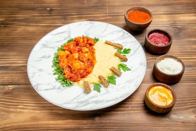 木製の机の皿にマッシュ ポテトと調味料を入れたおいしい肉のスライスの正面図肉料理ポテト フード パン