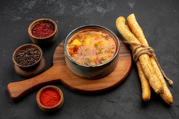 Vista frontale deliziosa zuppa di carne con pane e condimenti sullo spazio grigio
