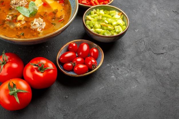 暗い背景に新鮮な野菜を使ったおいしい肉スープ