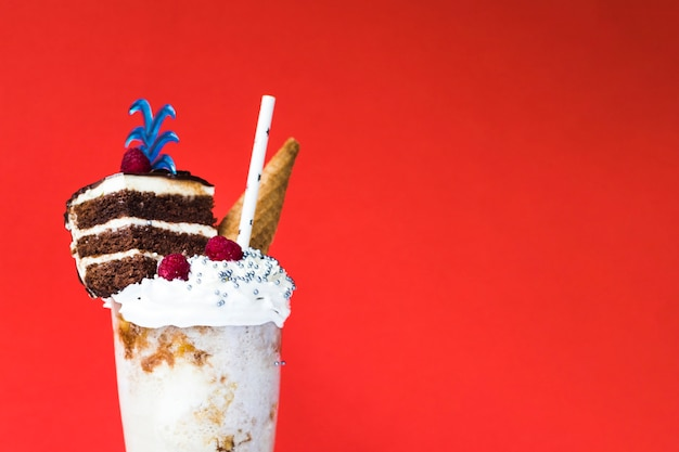 Front view of delicious milkshake with red background