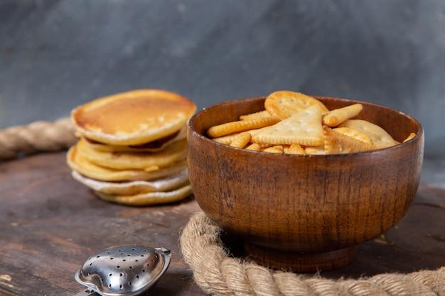 La vista frontale del muffin delizioso rotondo si è formata con le patatine fritte sulla superficie di legno