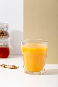 テーブルの上の正面のおいしいオレンジのスムージー