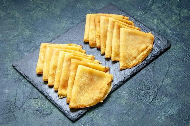 Вид спереди вкусные блины на темно-синем тесте выпечки печь пирог тесто для завтрака мясо