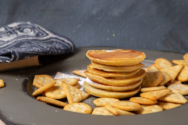 Front view of delicious pancakes with crackers on the grey surface