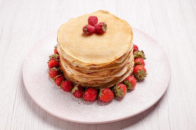 Pancake deliziosi di vista frontale con fragole rosse fresche su spazio bianco
