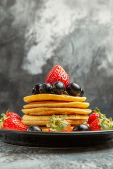 暗い表面のフルーツケーキデザートにフルーツとベリーが入ったおいしいパンケーキを正面から見る