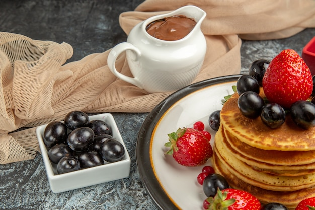正面図明るい表面にフルーツとベリーのおいしいパンケーキフルーツケーキ甘い