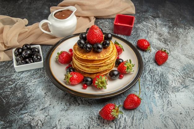 Vista frontale deliziose frittelle con frutta e bacche sulla torta di frutta superficie leggera dolce