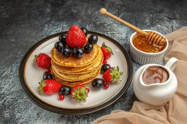 正面図明るい表面のケーキの甘い果物に蜂蜜と果物のおいしいパンケーキ