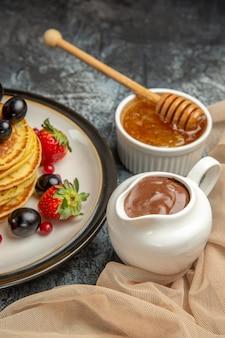 Vista frontale deliziose frittelle con miele e frutta sulla frutta dolce torta superficie leggera