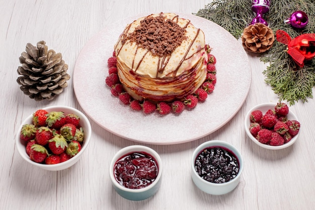 Vista frontale deliziose frittelle con gelatina e fragole su scrivania bianca torta torta biscotto frutta bacca dolce
