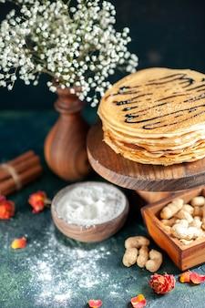 Vista frontale deliziose frittelle con noci su dolce al latte blu scuro colazione dolce mattina torta miele
