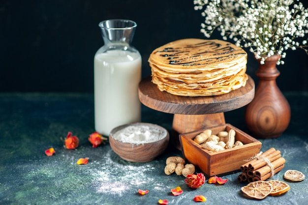 Front view delicious pancakes with nuts on dark blue milk dessert sweet morning pie cake honey breakfast